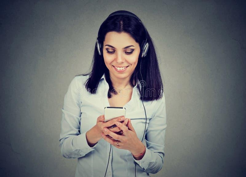 听到在手机的音乐的愉快的少妇 免版税库存图片