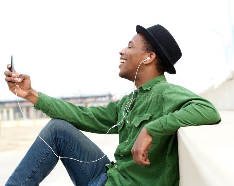 听到在手机的音乐的年轻人 免版税库存图片