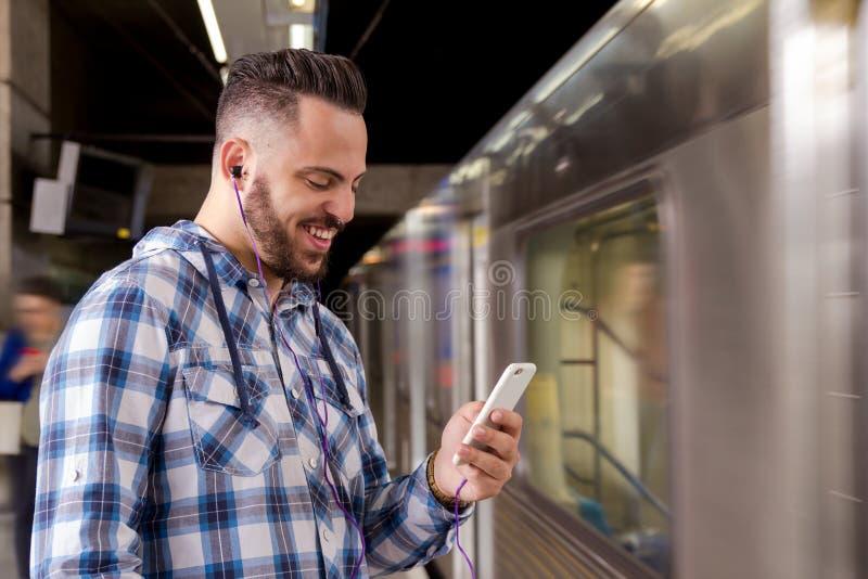 听到在智能手机的音乐的学生旅客等待的火车 休闲,通信,社会媒介的概念 库存图片