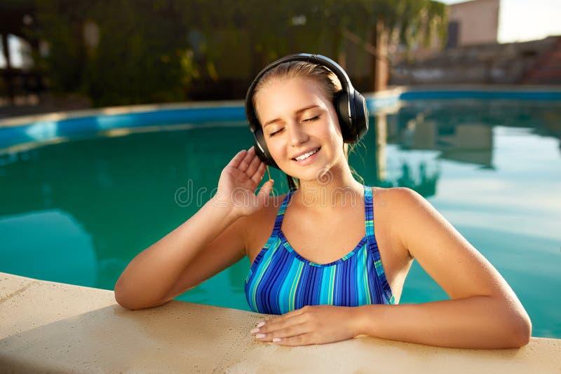 听到在沐浴在游泳池的耳机的音乐的轻松的微笑的妇女 白肤金发的女孩享受喜爱的歌曲与 免版税库存图片