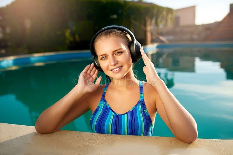 听到在沐浴在游泳池的耳机的音乐的轻松的微笑的妇女 白肤金发的女孩享受喜爱的歌曲与 免版税库存照片