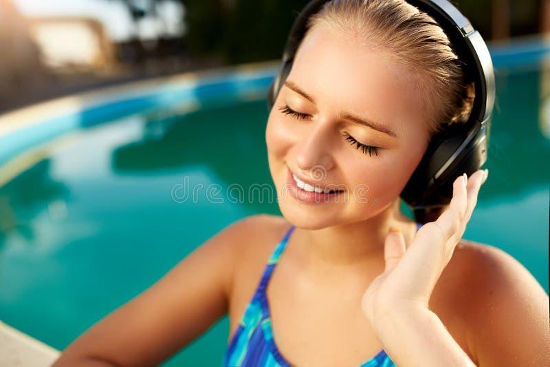 听到在沐浴在游泳池的耳机的音乐的轻松的微笑的妇女 白肤金发的女孩享受喜爱的歌曲与 库存照片