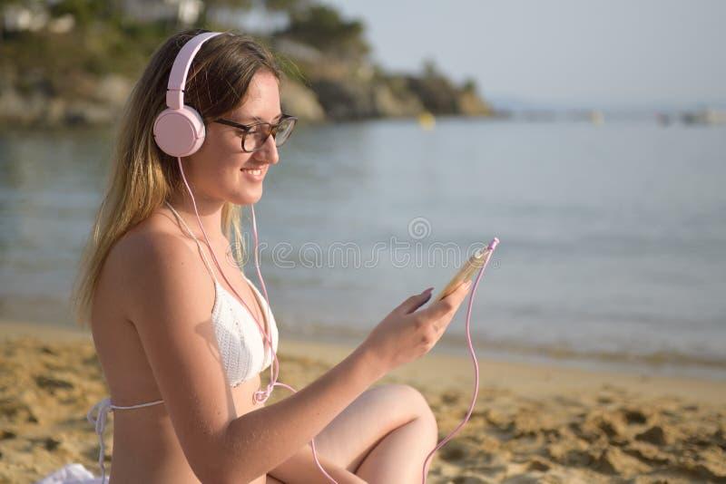 听到在海滩的音乐的年轻愉快的妇女 免版税库存照片