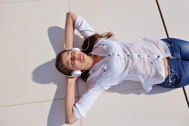 听到在白色耳机的音乐的女孩 免版税库存照片