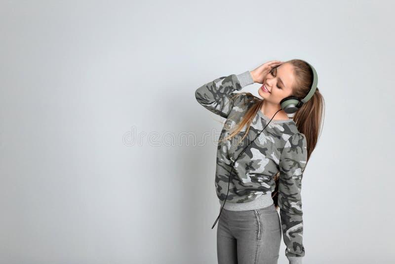 听到在白色背景的音乐的年轻女人 库存照片