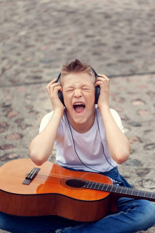 听到在耳机和尖叫的歌曲的音乐的少年 年轻人与吉他坐街道 免版税库存照片