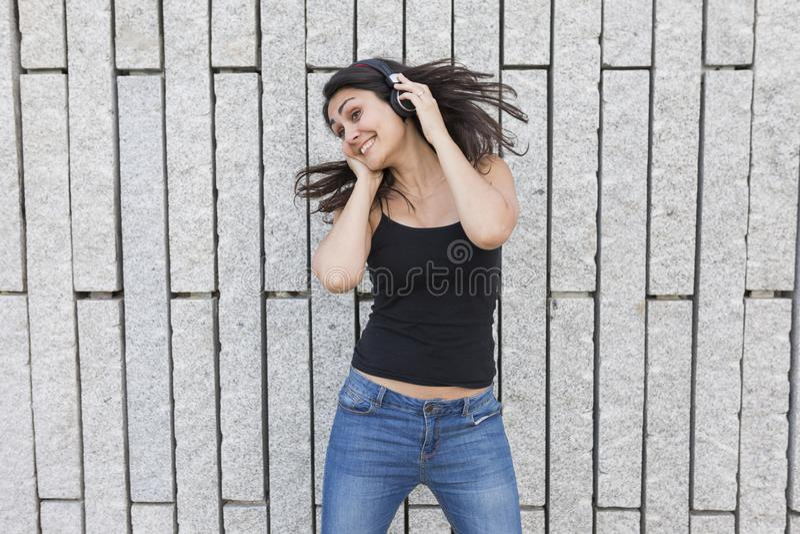 听到在耳机的音乐的一个美丽的少妇的画象 她跳舞,跳并且微笑着 她是佩带偶然 免版税库存照片