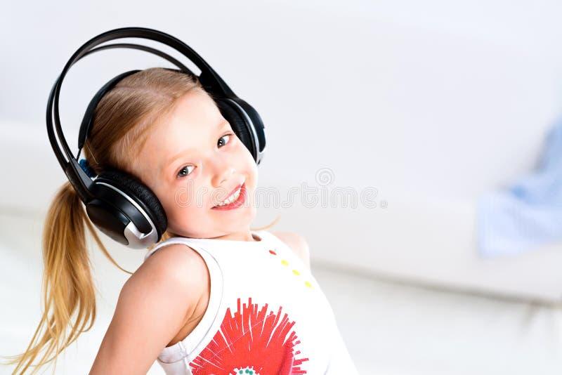 听到在耳机的音乐的俏丽的女孩 库存图片