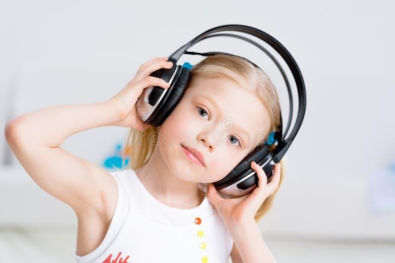 听到在耳机的音乐的俏丽的女孩 图库摄影