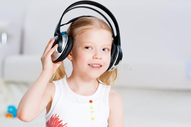 听到在耳机的音乐的俏丽的女孩 免版税图库摄影