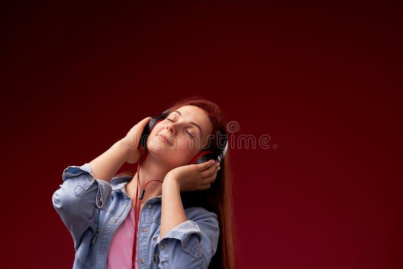 听到在耳机的音乐的女孩 牛仔裤的红发年轻美女和T恤杉愉快微笑在耳机, 免版税图库摄影