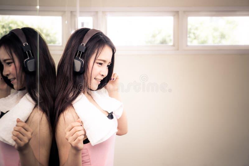 听到在耳机的音乐的妇女健身由镜子 免版税库存图片