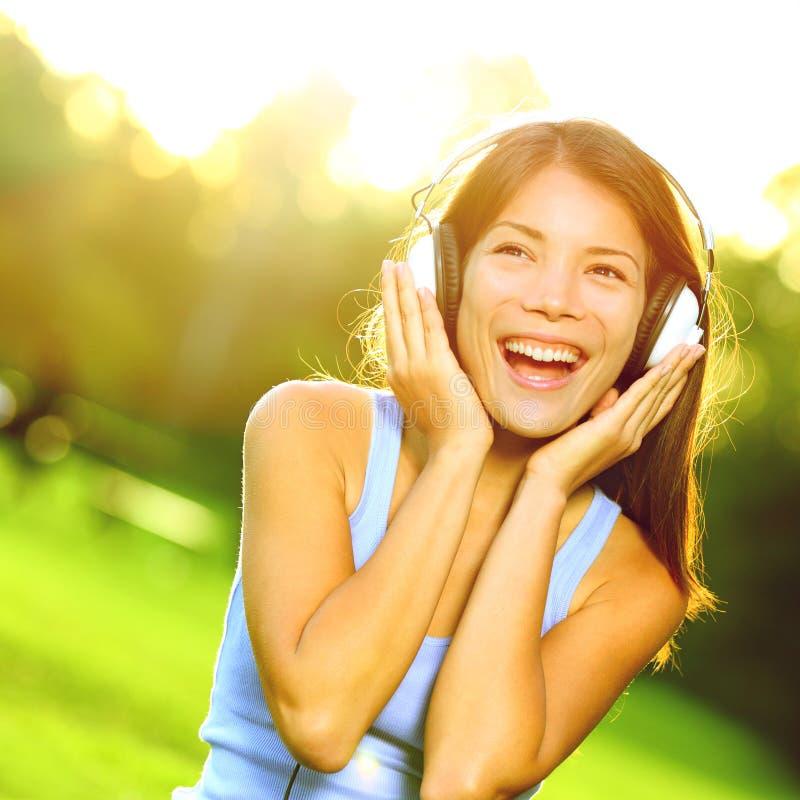 听到在耳机的音乐的妇女在公园 免版税库存照片