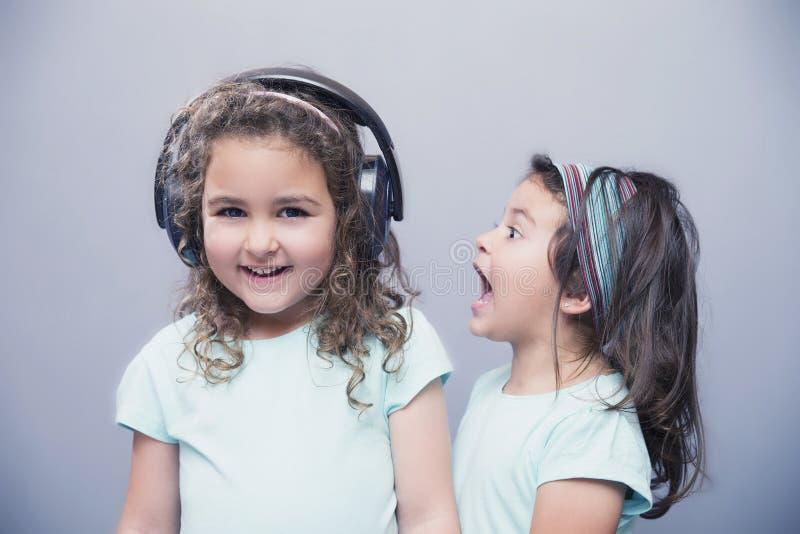听到在耳机的音乐的微笑的女孩有姐妹尖叫的 免版税库存图片