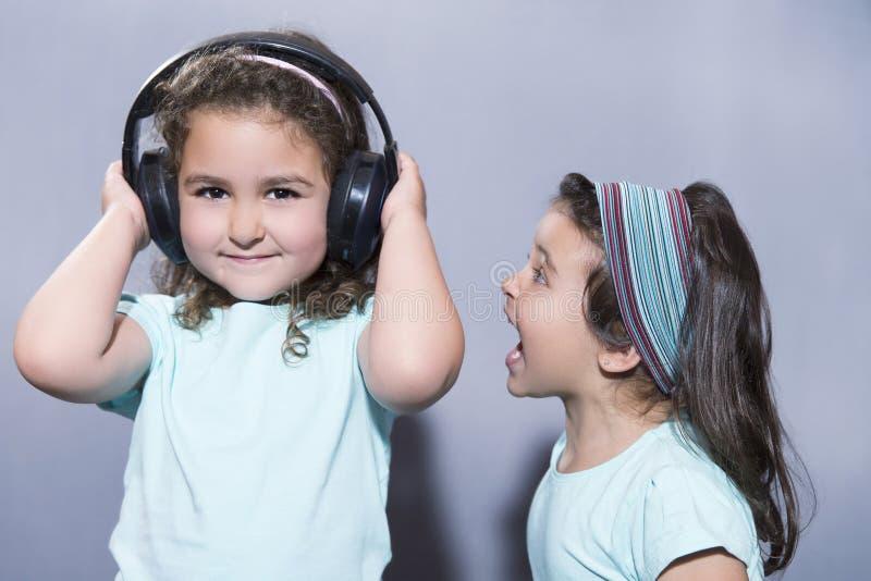 听到在耳机的音乐的微笑的女孩有姐妹尖叫的 库存照片