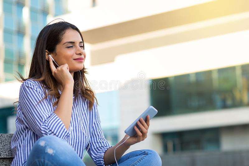 听到在耳机的音乐的微笑的妇女,享受晴朗的天气户外 免版税库存图片