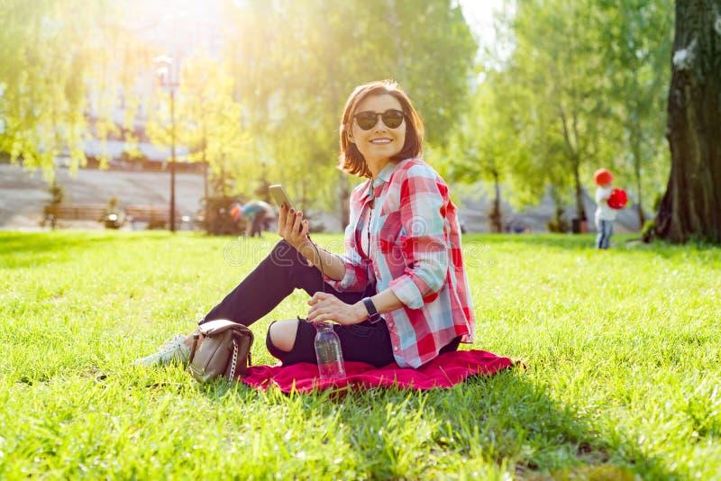 听到在耳机的音乐的成熟妇女 坐草在公园,休息享受自然 库存图片