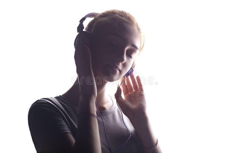 听到在耳机的音乐的浪漫女孩,放松在白色的少妇隔绝了背景 免版税库存照片