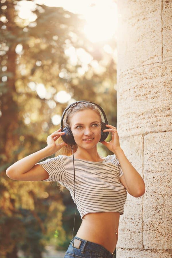 听到在耳机的音乐的行家女孩在夏天公园 库存照片