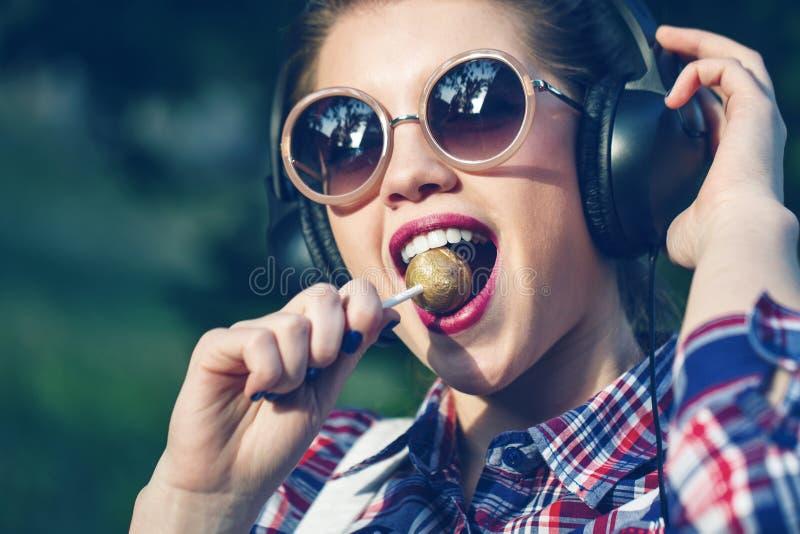 听到在耳机的音乐的行家女孩有棒棒糖的 图库摄影
