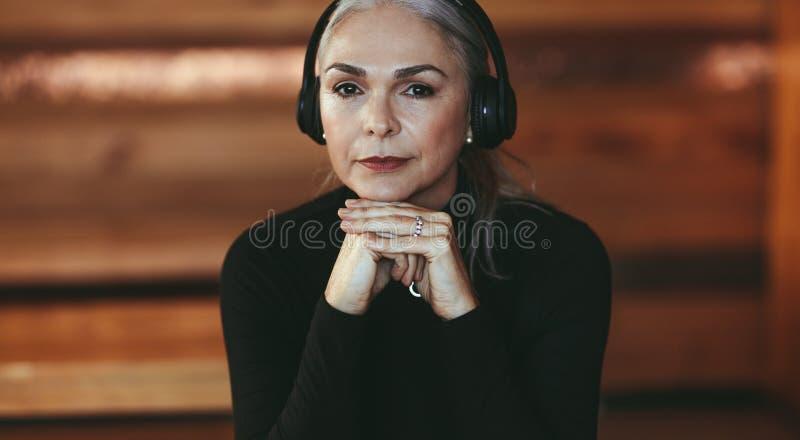 听到在耳机的音乐的资深妇女在咖啡馆 库存照片