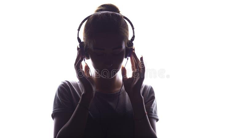 听到在耳机的音乐,年轻女人放松在白色背景,概念的一个浪漫女孩的剪影  免版税库存图片