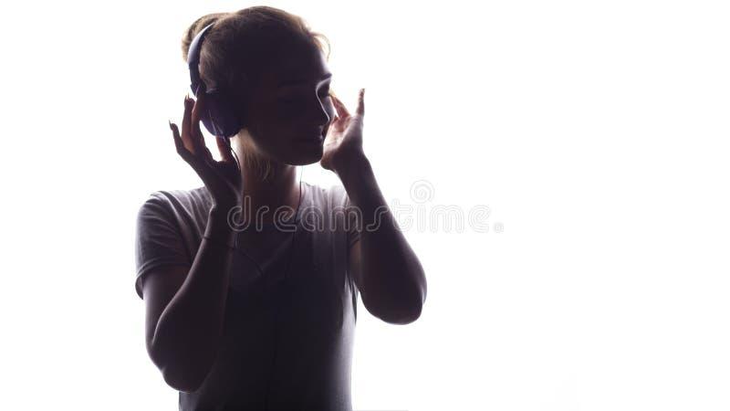 听到在耳机的音乐,年轻女人放松在白色背景,概念的一个浪漫女孩的剪影  免版税图库摄影