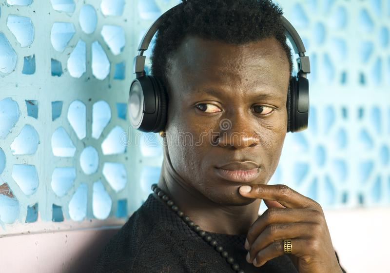 听到在被隔绝的黑耳机的音乐的年轻可爱和体贴的凉快的非裔美国人的人生活方式画象  免版税库存照片