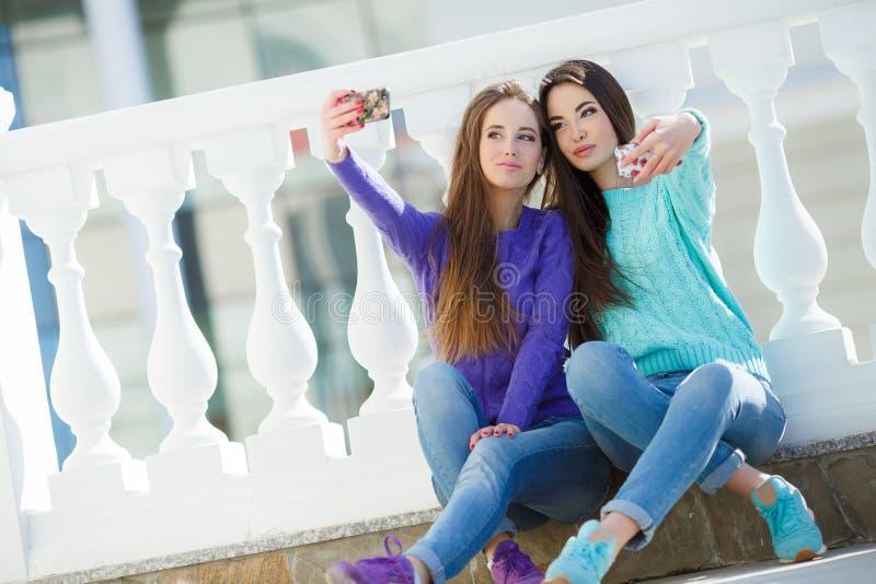 听到在他们的智能手机的音乐的两个女孩 免版税库存照片