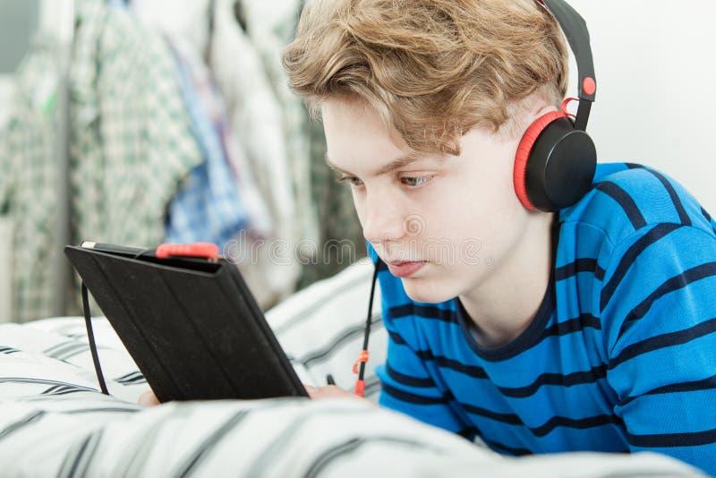 听到在他的片剂的音乐的十几岁的男孩 免版税库存照片