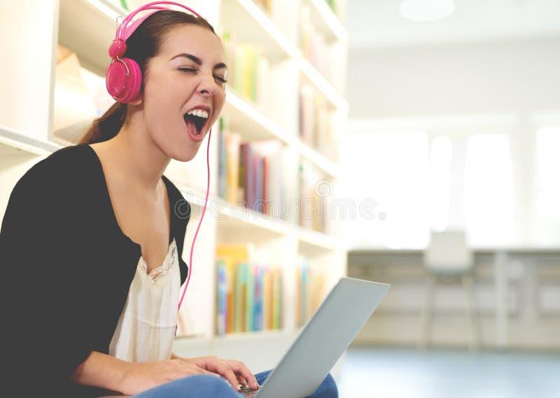 听到大声的音乐的滑稽的愉快的学生 库存图片