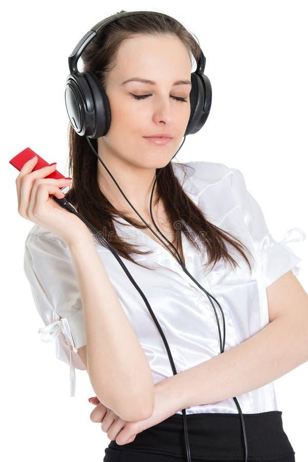 听到她喜爱的音乐的年轻美丽的妇女 库存图片