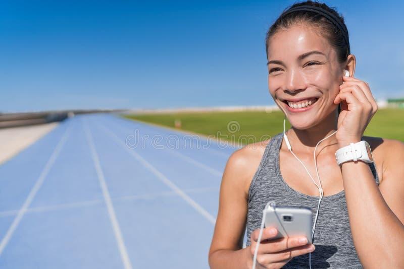听到连续刺激音乐的亚裔赛跑者 免版税库存照片