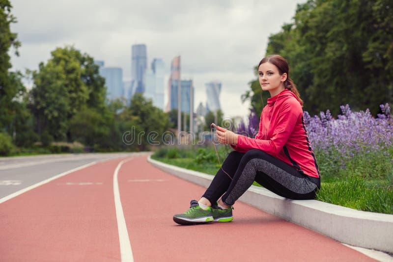 听到音乐和休息在跑步以后的年轻健身妇女 免版税库存图片