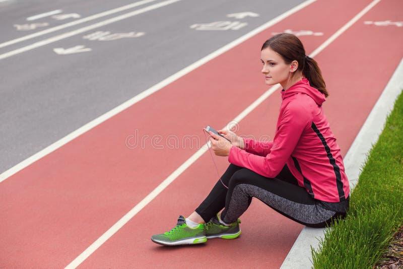 听到音乐和休息在跑步以后的年轻健身妇女 库存图片