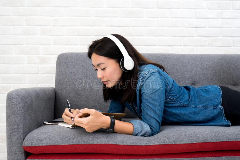 听到音乐和写日志的妇女在沙发 免版税库存图片