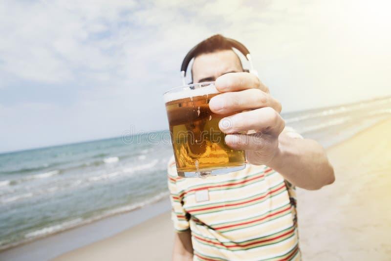 听到音乐和在海滩的饮用的啤酒 库存照片