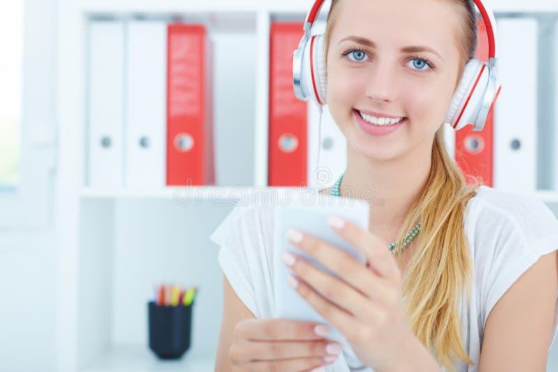 听到音乐和拿着白色智能手机的年轻美丽的微笑的妇女特写镜头画象  免版税库存照片