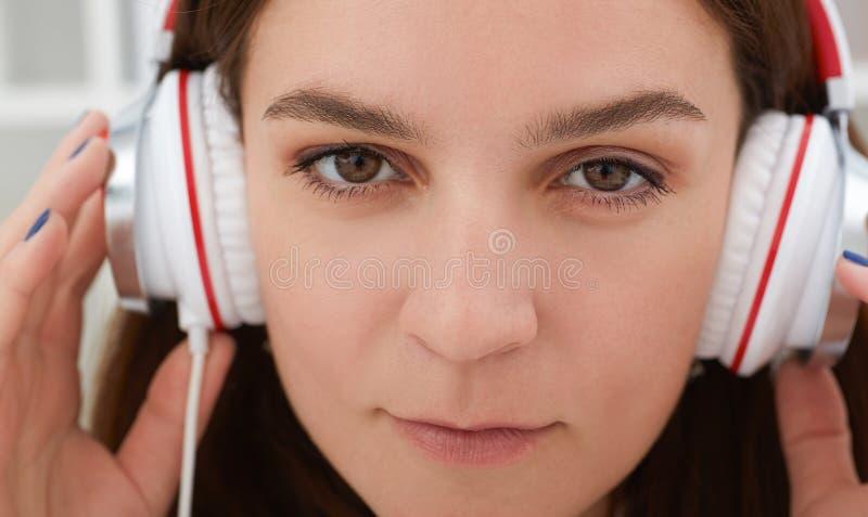 听到音乐和拿着耳机的年轻美丽的深色的妇女特写镜头画象  库存照片