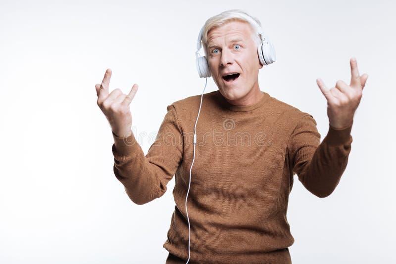 听到音乐和显示垫铁的迹象老人 图库摄影