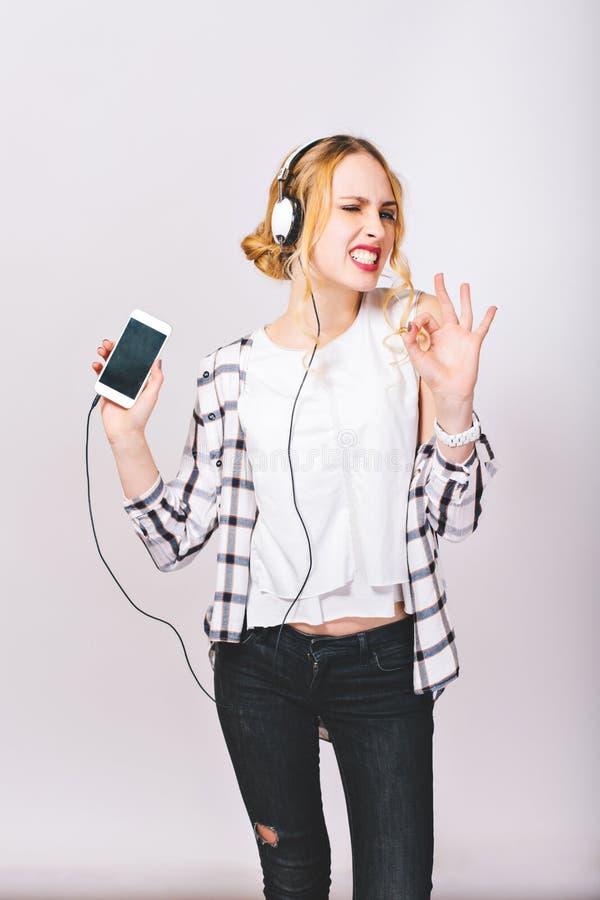听到音乐和非常享有她扣人心弦的生活的高兴逗人喜爱的快乐的女孩的图象 愉快和正面心情 免版税图库摄影