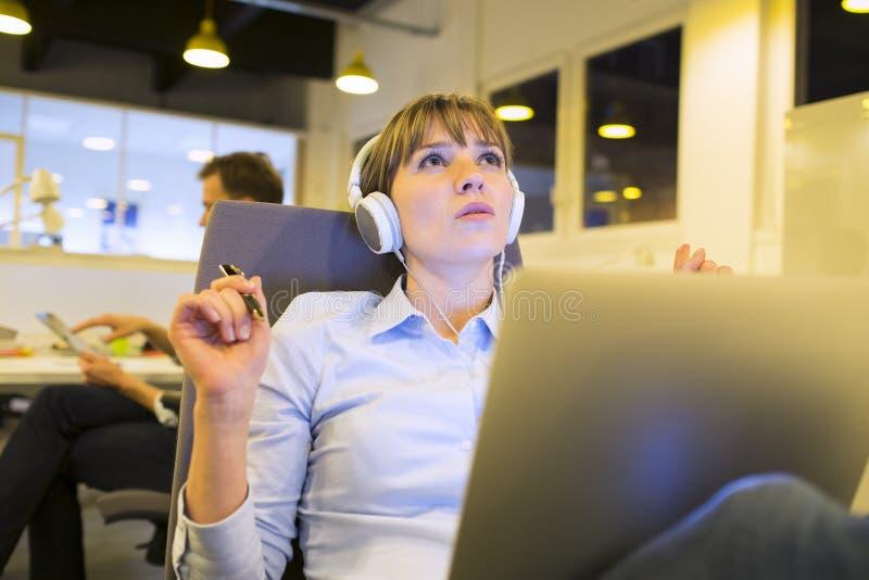 听到音乐的一个少妇在工作 免版税库存照片