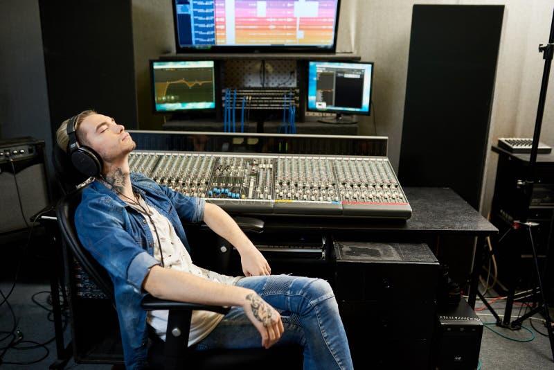 听到音乐的人在演播室 免版税库存照片