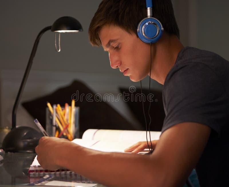 听到音乐的十几岁的男孩,学习在书桌在卧室在晚上 库存图片
