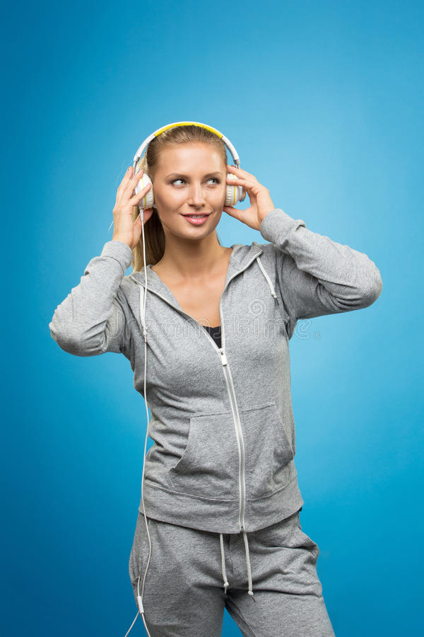 听到音乐的可爱的年轻女运动员 免版税图库摄影