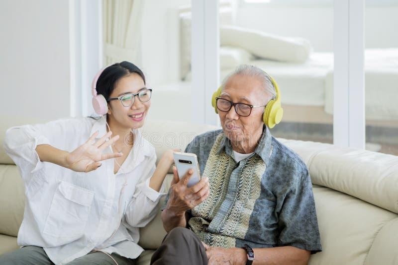听到音乐的妇女和年长人 免版税库存照片