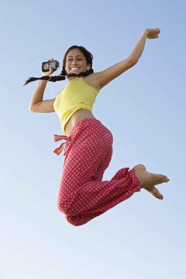 听到音乐的妇女,当跳跃时 免版税库存图片