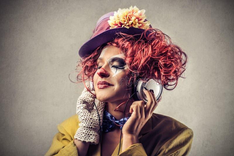 听到音乐的小丑 库存图片