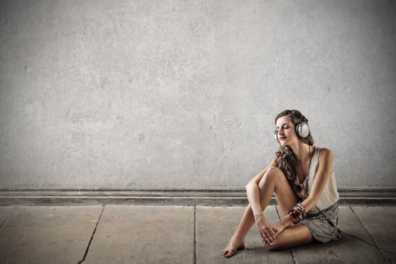 听到音乐的少妇 免版税图库摄影