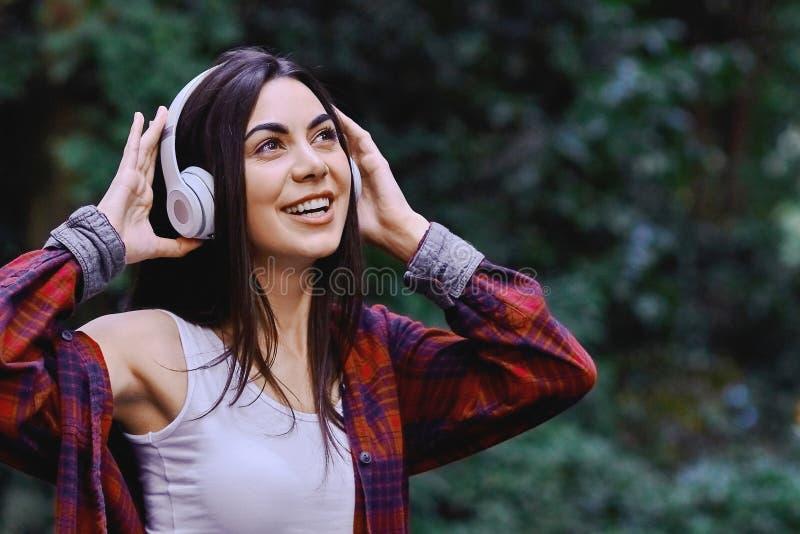 听到音乐的年轻微笑的妇女,通过在她的头的耳机 库存图片